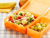 Lunch box with salad and grapes