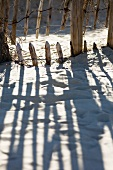 Shadow of wooden fence on sand