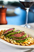 Sliced Herb Crusted Lamb Served Over White Beans