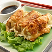 Three Potstickers with Chopsticks and Soy Sauce