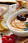 A Bowl of Hummus with Olives, Tomatoes and Toasted Pita Bread Triangles
