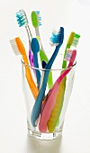 Assorted Colorful Toothbrushes in a Glass; White Background
