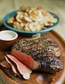 Steak au Poivre (Peppered Steak) Partially Sliced on a Cutting Board; Potato Chips