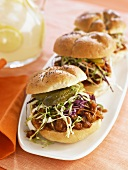 Barbecue Beef Sandwiches Topped with Slaw and Pickles on a Platter