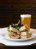 Sandwich mit Huhn, Tomate und Salat, dazu ein Glas Bier