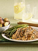 Grilled Chicken Breasts with Asparagus on a Serving Dish; Potatoes and Lemonade