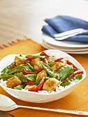 Chicken Stir Fry with Snow Peas and Red Peppers Over Rice in a Serving Bowl