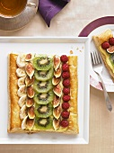 Winter Fruit Tart on a Platter; Slice on a Plate with a Fork