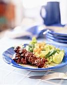 Meat skewers and leaf salad