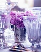 Violette Blumendeko auf gedecktem Tisch