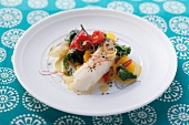 Cod with vegetables, lemon sauce and chili strings