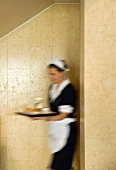 Blurred waitress in traditional uniform hurrying with full tray against marble-clad, sand-coloured wall