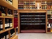 Verkaufsraum einer edlen Weinhandlung mit raumhohen Flaschenregalen aus Holz