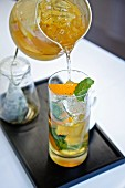 Orange, Pear and Mint Iced Tea Pouring From a Pitcher into a Glass