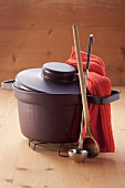 A cooking pot, a wooden spoon and a ladle