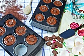 Unbaked chocolate muffins in muffin tins with chocolate pieces in the middle