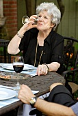 A woman drinking a glass of wine on a terrace
