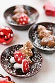 Mini gingerbread Christmas trees and decorative toadstools in wooden bowls dusted with icing sugar