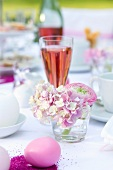Pink table decorations made with hortensias, eggs and a glass of champagne