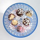 Petit fours with chocolate icing, sugar pearls and snowflakes