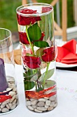 Red roses with pebbles and crayfish in glass vase