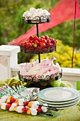 Cake stand with marshmallows and strawberries on a table outside