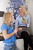 Blonde Frau auf dem Küchenschrank sitzend unterhält sich mit ihrer Freundin