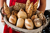 Hands holding bread basket with various bread rolls