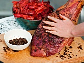 Rubbing barbecue marinade into leg of wild boar