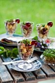 Potato and ham salad with grapes and cress in glasses