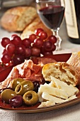 Antipasto Appetizer with Provolone, Prosciutto, Olives, Ciabatta Bread, Red Grapes and Red Wine
