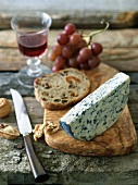 Fourme d'Ambert Cheese with Fruit Bread and Walnuts on a Board with a Knife