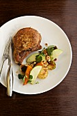 Pork Chop with Veggies and Apple Slices; On a White Plate with Fork and Knife