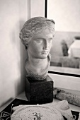 Antique bust in front of window