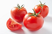 A slice of tomatoes and three whole tomatoes