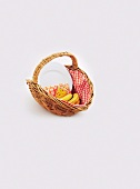 A wicker basket with bananas, paper cups, napkins and plates