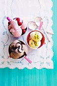 Home-made raspberry ice cream, passion fruit ice cream and chocolate ice cream in bowls