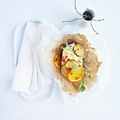 Cod fillets with citrus fruits and chilli baked in parchment paper