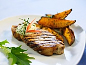 A grilled chop with herb butter and potato wedges