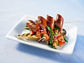 Sausages on a skewer serve with toasted bread and tomato salad