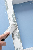 Alter, weiss lackierter Holzrahmen wird mit Spachtel bearbeitet