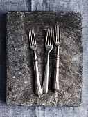 Three forks on a stone platter (seen from above)
