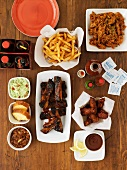 Various fast food dishes (spare ribs, chicken wings, pulled pork, chips)