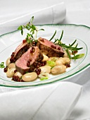 Saddle of lamb on a bed of bean salad