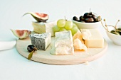 A cheese platter with grapes, figs and olives