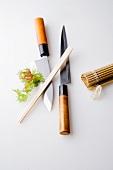 Japanische Messer, Essstäbchen und Bambusmatte für Sushi