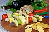 Cheese, fruit and vegetables on sticks with crackers, bread and red wine
