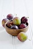 Fresh plums on a wooden bowl