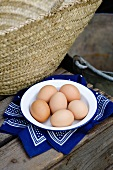 Brown chicken eggs on a plate and cloth