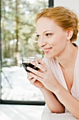 A young woman drinking a cup of coffee
